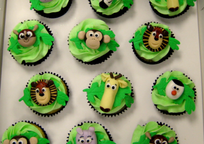 Green buttercream cupcakes with animal face toppers