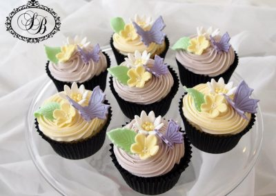 Lilac and yellow buttercream cupcakes with butterflies & blossoms