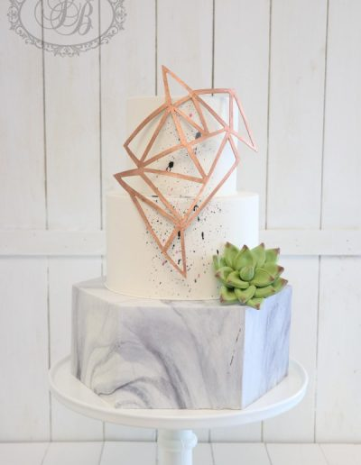 Marble hexagonal wedding cake with rose gold geometric