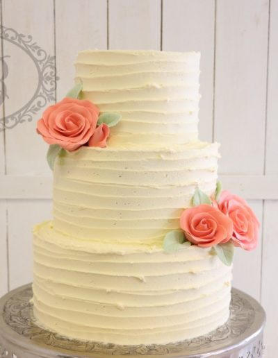 Linear buttercream wedding cake with apricot sugar flowers