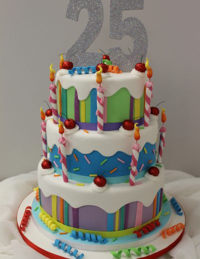 Colourful 25th celebration cake with candles & cherries