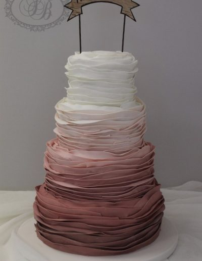 Dusty pink ombre ruffle wedding cake with banner