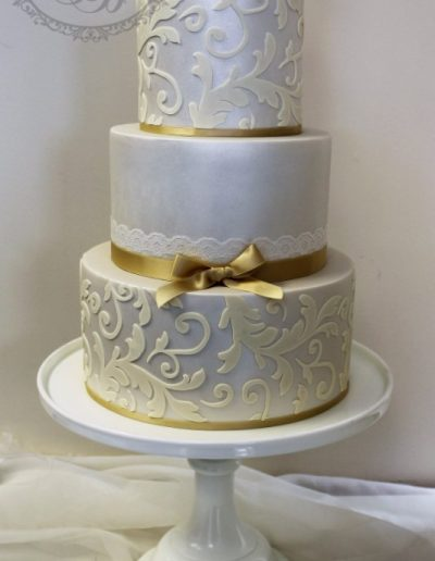 Silver and gold wedding cake with damask and lace