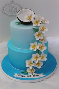 2 tier blue cake with frangipanis and coconut