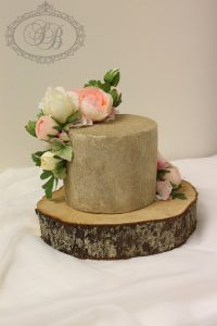 Gold glitter and flowers cake on log base