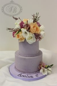 2 tier purple buttercream cake with flowers