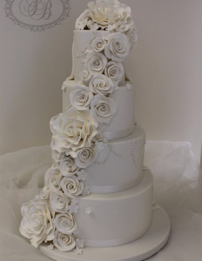 Full white wedding cake with drape and sugar flower cascade