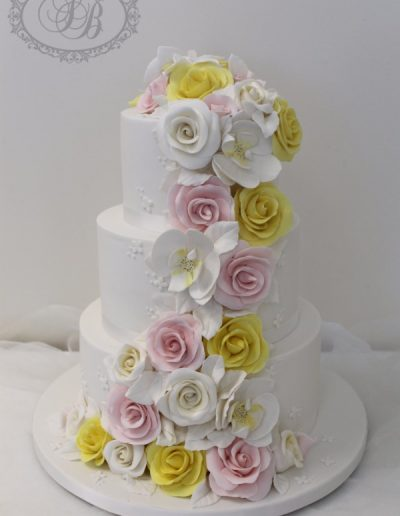 3 tier wedding cake with pink and yellow sugar flower cascade
