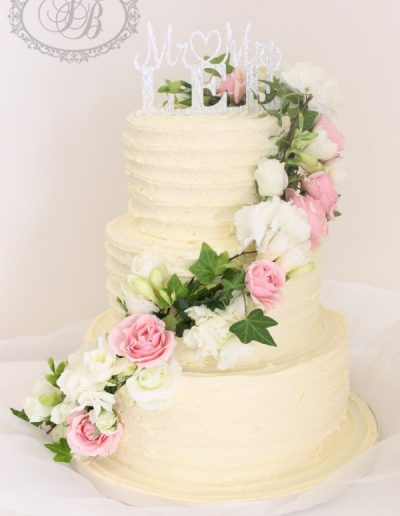 Ribbed buttercream wedding cake with rose and ivy cascade