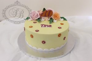 Yellow fondant cake with pink and orange flowers
