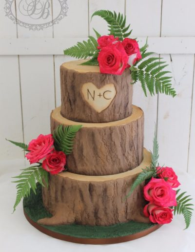 3 tier wooden log wedding cake with roses and ferns