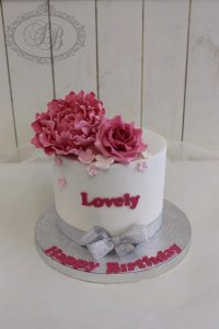 White cake with silver ribbon and pink sugar flowers