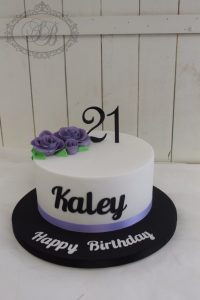 1 tier white cake with purple roses and black writing