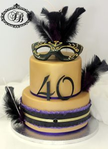 2 tier gold cake with mask and feathers