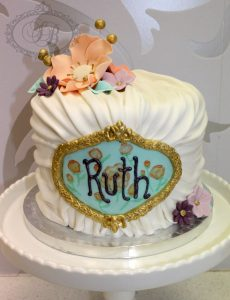 1 tier white pleated cake with detailed monogram plaque with sugar flowers