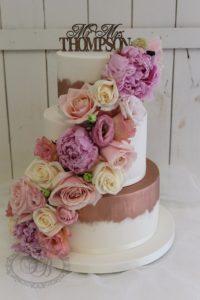 Rose gold brushed wedding cake with flower cascade