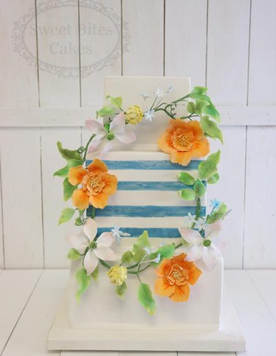 Floral wreath and blue stripes wedding cake