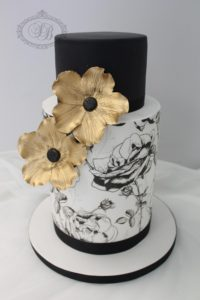 Black and white print wedding cake with gold flowers