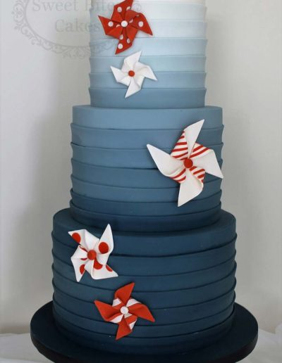 Navy ombre wedding cake with orange fans