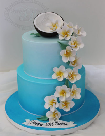 Blue airbrushed cake with coconut and frangipanis