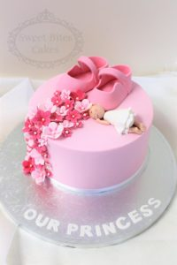 Baby girl shoes and blossoms cake