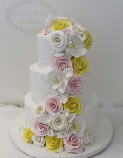 White wedding cake with yellow and pink flowers
