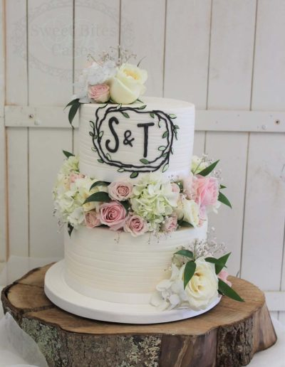 Rustic flower blocked wedding cake with monogram