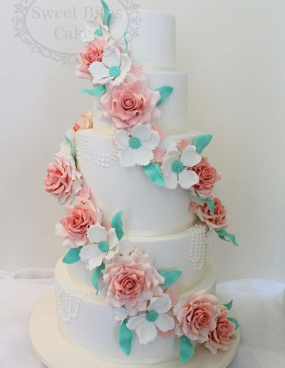 5 tier wedding cake with peach and blue flower cascade