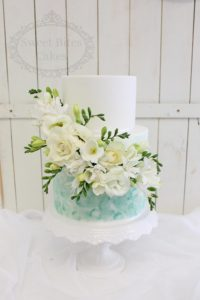 Mint and white wedding cake with fresh flowers