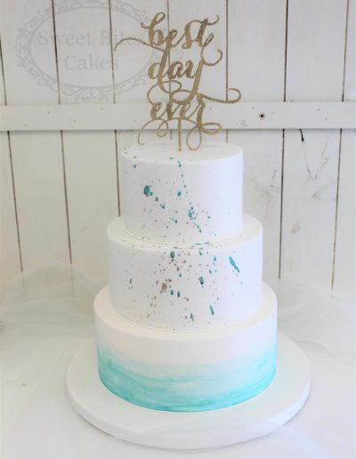 White and blue wedding cake with splatter