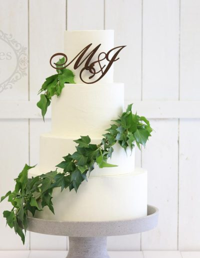 White ganache wedding cake with ivy