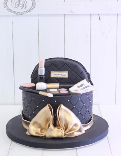 Black and gold makeup bag cake