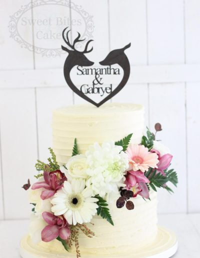 Buttercream wedding cake with deer couple topper