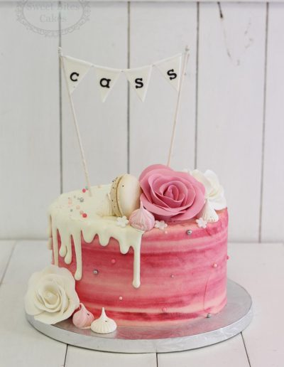 Pink and white drip cake with bunting