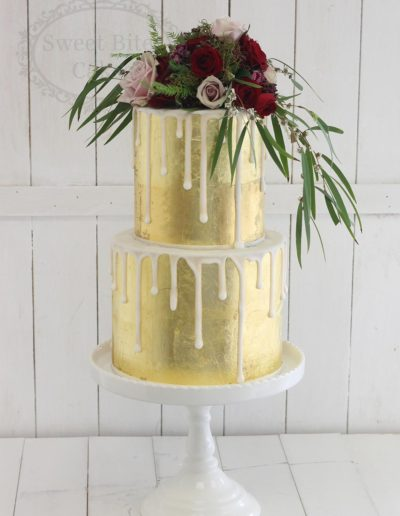 Gold foil wedding cake with white drip