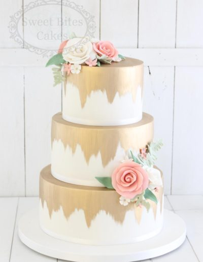 Gold brushed wedding cake with sugar roses