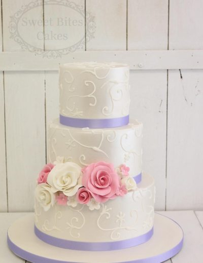 Wedding cake with piping and purple ribbon