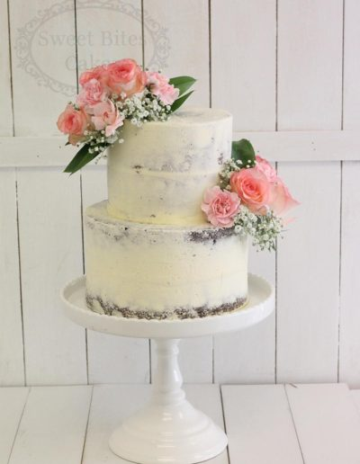Semi naked buttercream wedding cake with flowers