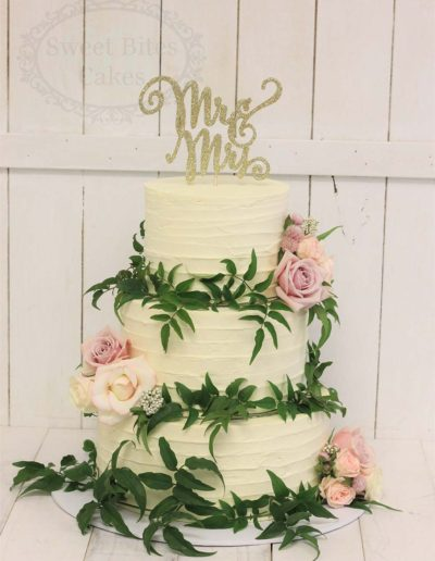Buttercream wedding cake with greenery