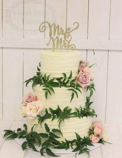 Buttercream wedding cake with greenery