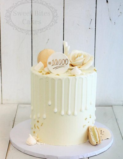 White and gold drip cake with macarons