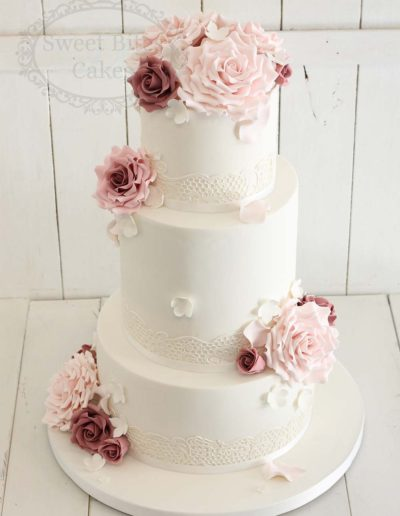 3 tier white lace wedding cake with sugar roses