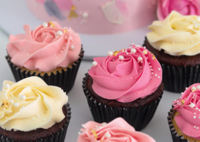 pink light pink white cupcakes with white and gold sprinkles